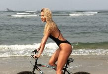 Bikini clad Lisa Haydon rides a bicycle on the beach