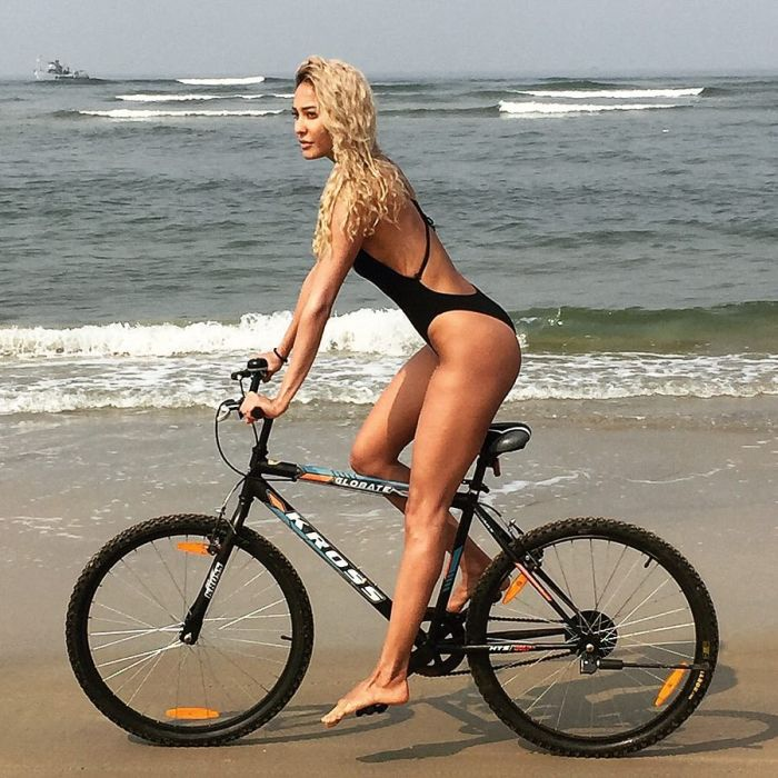 Bikini clad Lisa Haydon rides a bicycle on the beach