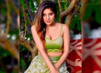 Sakshi Agarwal sitting on Elephant who is bathing her by spraying water