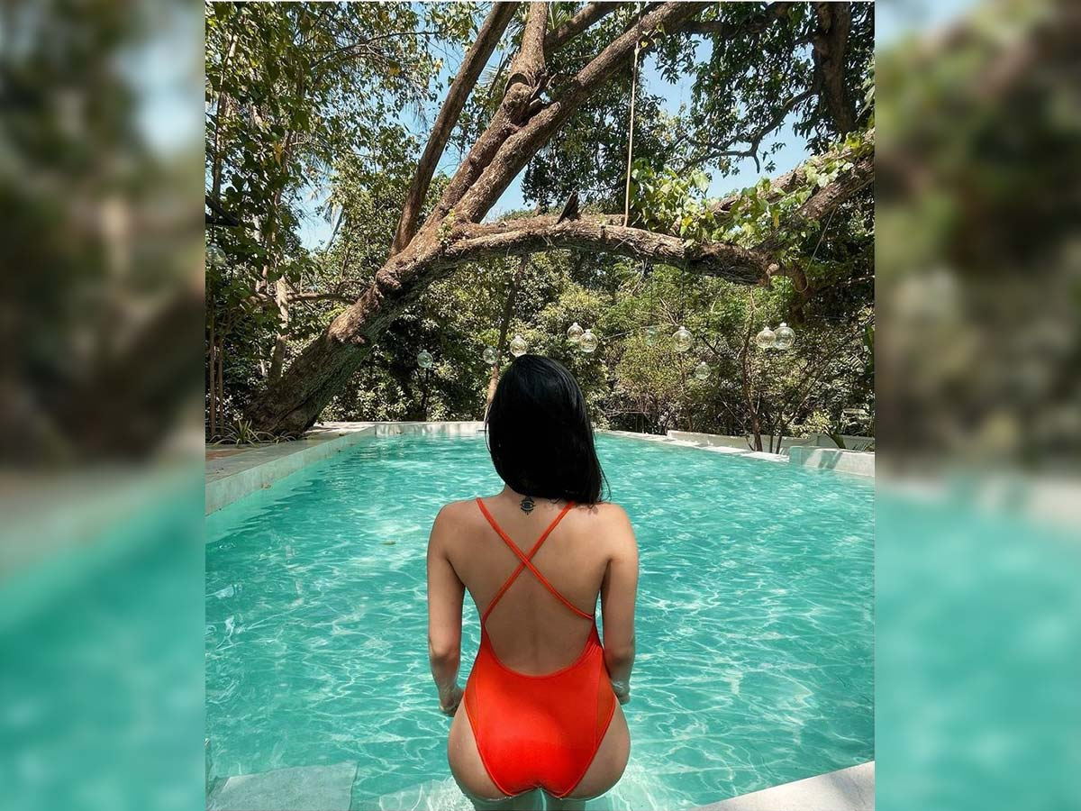 Bikini girl seductive back pose in pool